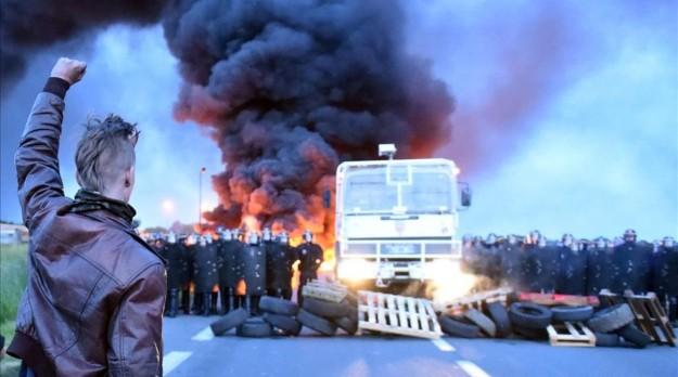 Topshot - Un manifestant brandit son poing alors que la police anti-émeute se préparent à intervenir pour disperser des travailleurs de la raffinerie tenant un blocus du dépôt pétrolier de Douchy-les-Mines pour protester contre les réformes proposées du travail du gouvernement le 25 mai 2016 les travailleurs des raffineries ont intensifié les grèves qui menacent de paralyser la France semaines avant le tournoi Euro 2016 que le gouvernement a décidé de rompre leurs blocus escalade trois mois remorqueur de la guerre sur les réformes du travail AFP PHOTO FRANCOIS LO PRESTI