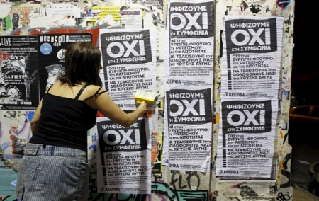 "A woman puts up referendum campaign posters with the word ""No"" in Greek in Athens"