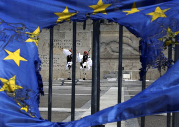 guardias-presidenciales-griega-fotografiados-a-traves-de-una-bandera-de-la-ue-rota-en-atenas-reuters